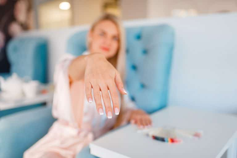 Customer shows perfectly made nails in beauty shop