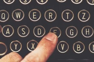 Finger on vintage typewriter machine