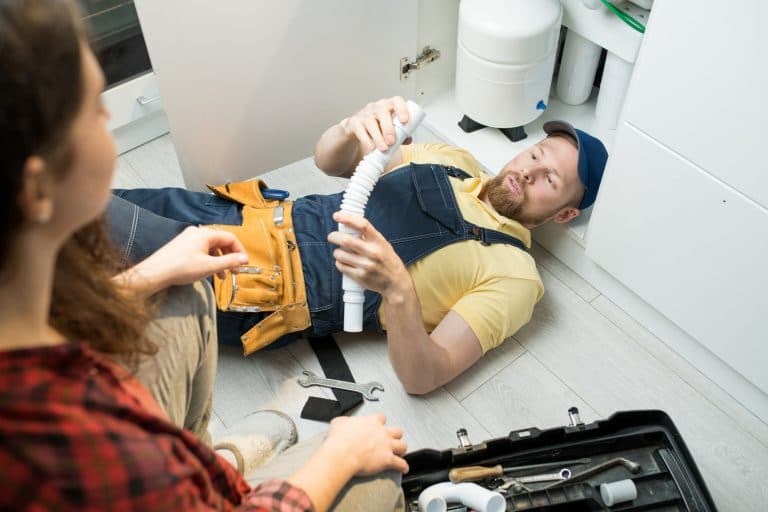 Young plumber changing trap under sink